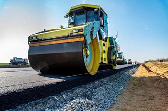 a road roller is constructing an asphalt road.
