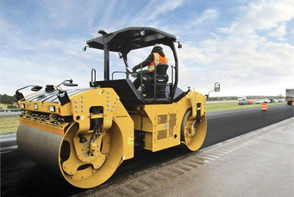 A worker is driving a double drums road roller.
